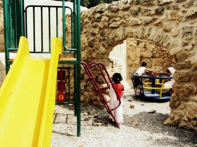 Children play on structures in Abwein playground