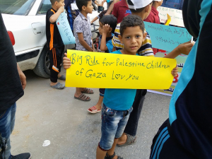 "Child holding a sign that says ""Big Ride for Palestine Children of Gaza Love You"""