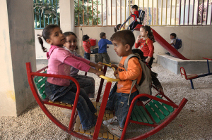 Young children play on slides and swings