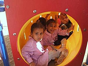 Smiling children in playground tunnel