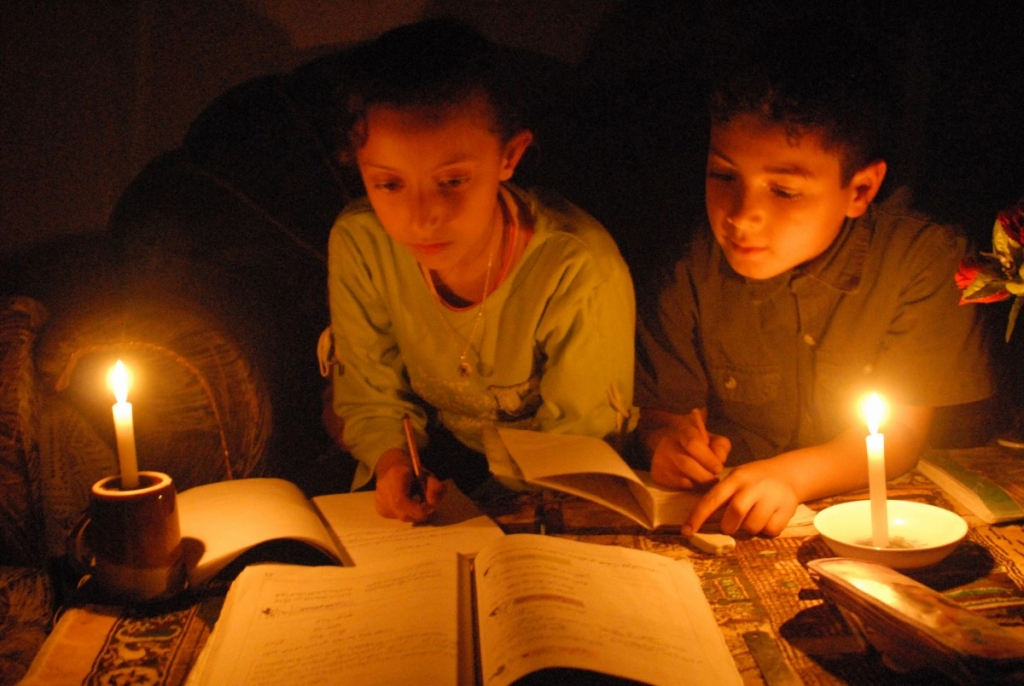 Kids in Gaza doing school work by candlelight.