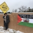 Dr Mona El-Farra standing next to a Palestinian flag in Santa Fe, New Mexico
