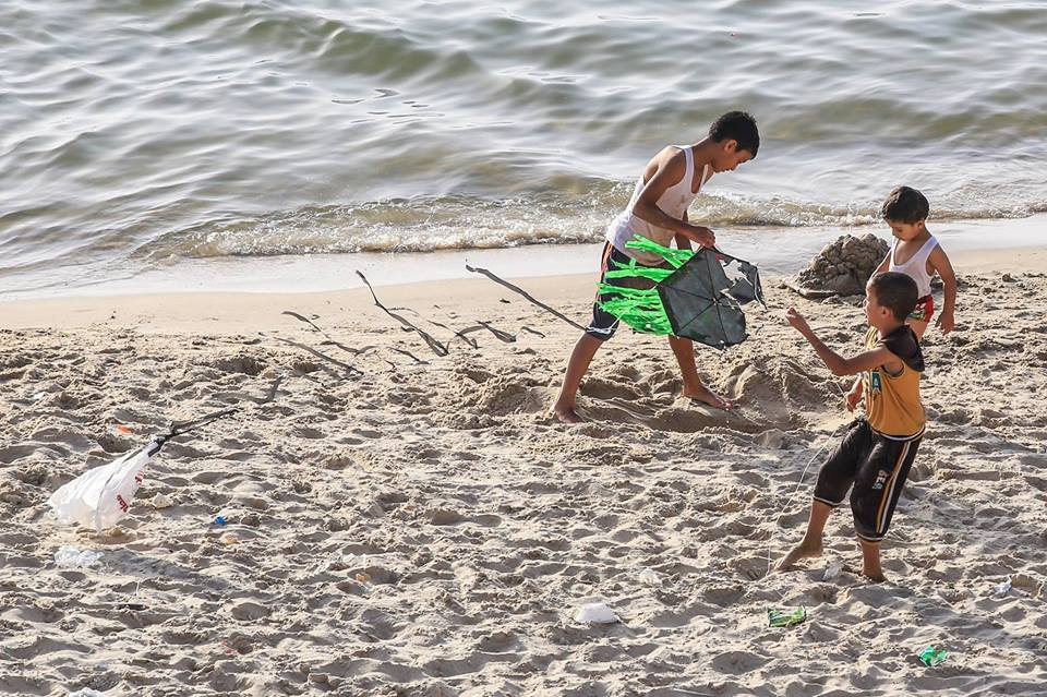 Children in Gaza play with kites on the beach