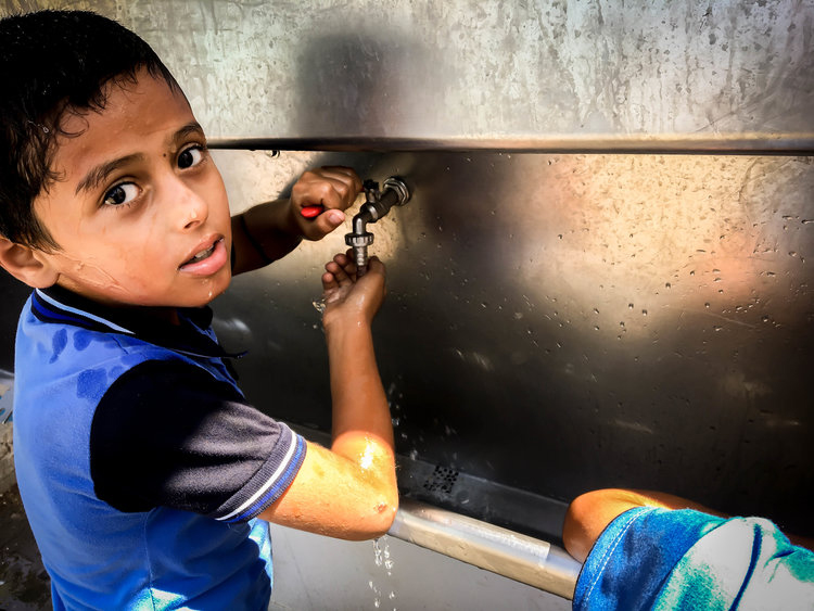 Child in Gaza getting safe, clean water