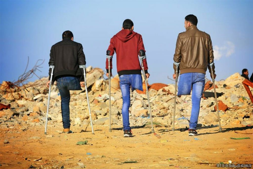 3 youth in Gaza on crutches in front of rubble